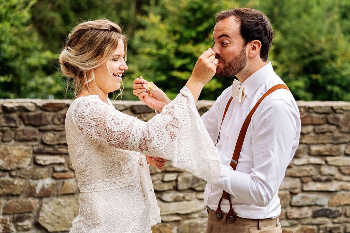 bruidstaart aansnijden, bruidstaart eten, bohemian bruiloft, trouwen in de ardennen, trouwfotograaf ardennen