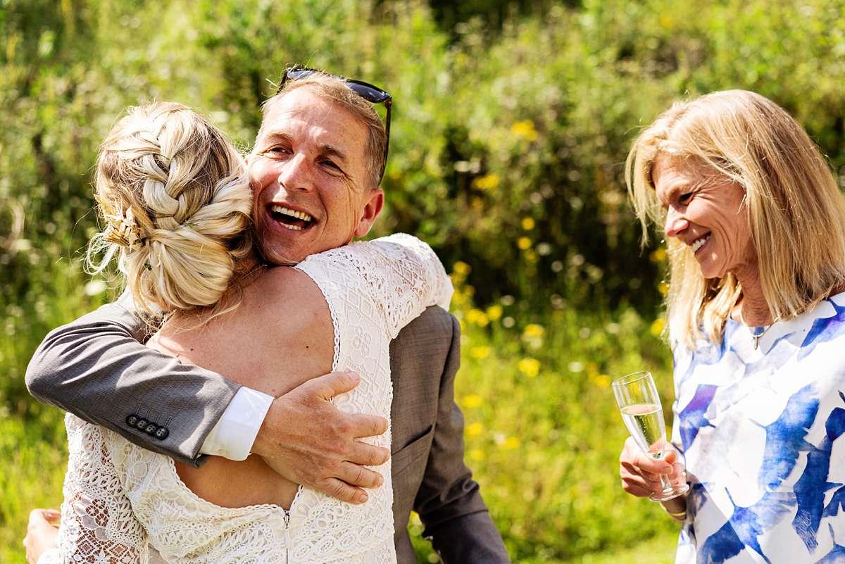 trouwen ardennen, trouwen sechery, trouwceremonie buiten, internationale bruiloft, lachend bruidspaar, echte momenten, vader omhelst dochter, buiten trouwen, confetti bruiloft, journalistieke foto, bruidsfotograaf ardennen, bruidsfotograaf belgie, trouwfotograaf belgie