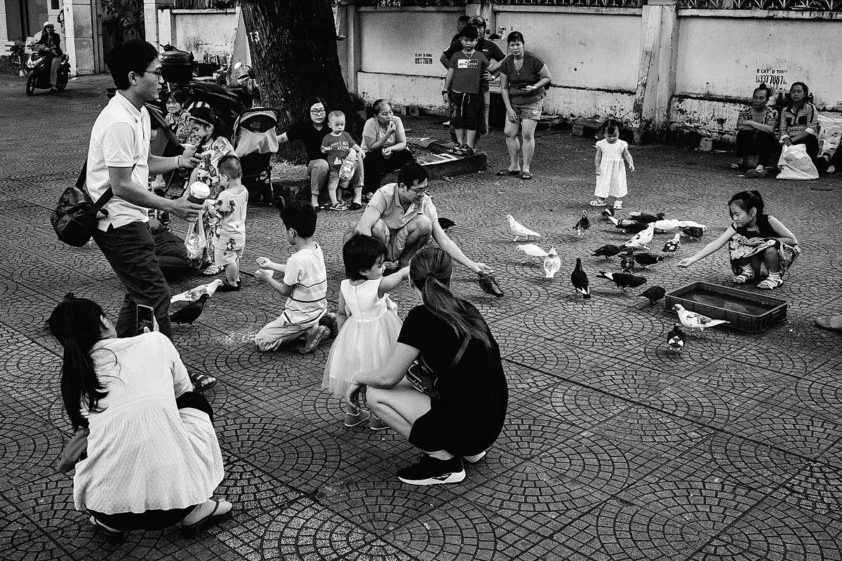 RUUDC Fotografie, reisfotograaf, straatbeeld in Ho Chi Minh, kinderen spelen op straat, duiven voeren